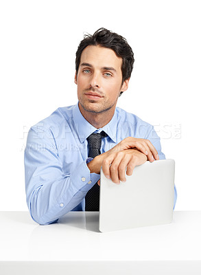 Buy stock photo Studio shot of a handsome businessman sitting at his desk with a tablet