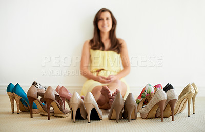 Buy stock photo Portrait of a beautiful young woman sitting on the floor surrounded by shoes