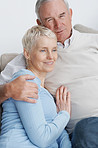 Senior man hugging his wife while on a couch