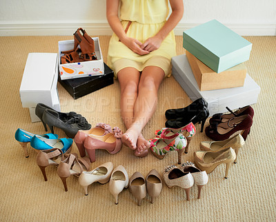 Buy stock photo Cropped image of a woman sitting in her room surrounded by shoes