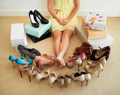 Buy stock photo Cropped image of a woman sitting on the floor surrounded by shoes