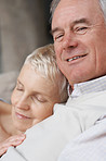 Closeup of an elderly man with wife resting on chest