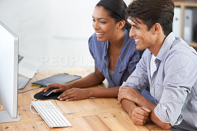 Buy stock photo Cropped shot of two young colleagues using a computer