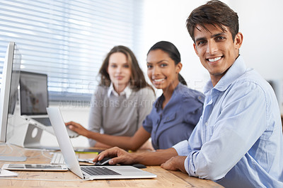 Buy stock photo Cropped shot of three young colleagues working at a desk