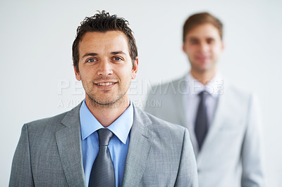 Buy stock photo Portrait of a handsome young executive smiling with a colleague blurred in the background
