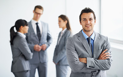 Buy stock photo A handsome young businessman standing beside a window while his colleagues talk in the background