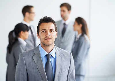Buy stock photo Portrait of a handsome young businessman with his colleagues talking in the background