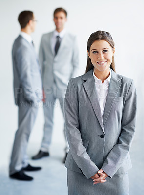Buy stock photo A pretty young businesswoman smiling at you while colleagues stand in the background
