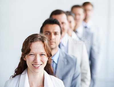 Buy stock photo A pretty businesswoman standing with her colleagues in a line behind her