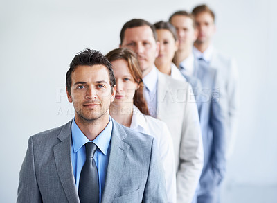 Buy stock photo A group of businesspeople standing in line and looking determined