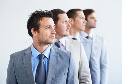 Buy stock photo A line of businessmen looking away thoughtfully - Ambition