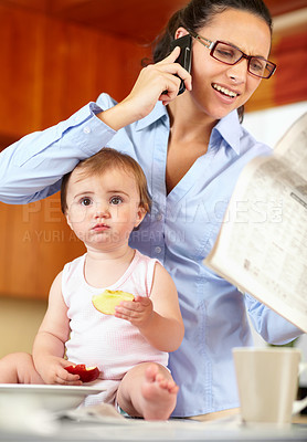 Buy stock photo Shot of a frustrated-looking single mom feeding her baby while trying to talk on the phone and holding a newspaper