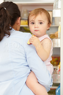 Buy stock photo Shot of a cute baby being held by it's caring mom in front of an open fridge