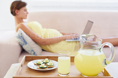 Buy stock photo A healthy meal next to a pregnant woman lying on the couch with a laptop