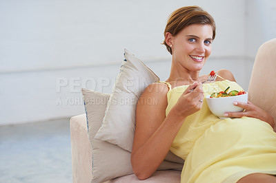 Buy stock photo Portrait of a young pregnant woman enjoying a healthy salad while relaxing on the couch