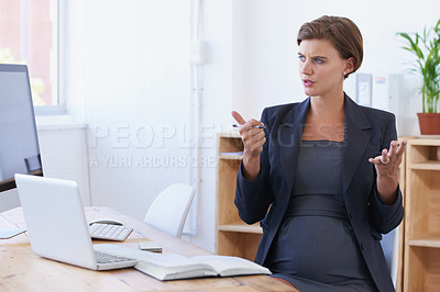 Buy stock photo A pregnant businesswoman counting on her hands while sitting at her office desk