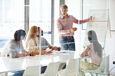 Buy stock photo A group of businesspeople listening to their team leader