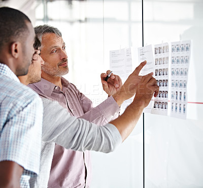 Buy stock photo Shot of a group of male colleagues discussing work in the office