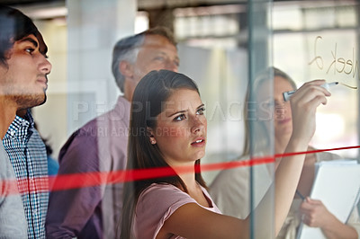Buy stock photo A young businesswoman writing down plans on a glass pane while her associates look on
