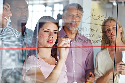 Buy stock photo A group of business colleagues brainstorming together at a glass wall