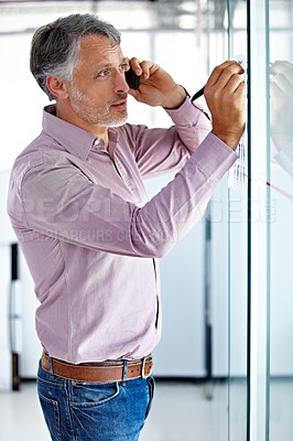 Buy stock photo A mature businessman talking on his mobile while writing on a board