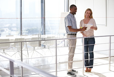 Buy stock photo Two business associates talking while looking over some paperwork