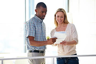 Buy stock photo Two business colleagues talking while looking over some documents