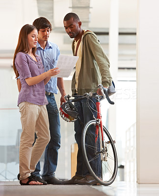 Buy stock photo A young bike messager deliver mail to two young business executives