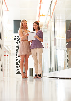Buy stock photo Two businesswomen discussing some paperwork