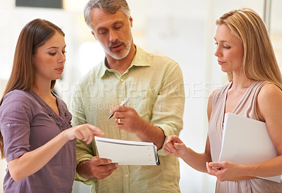 Buy stock photo Shot of three business professionals standing and going through some paperwork together