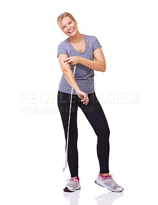 Buy stock photo Studio shot of an attractive young woman measuring her workout progress with a tape measure