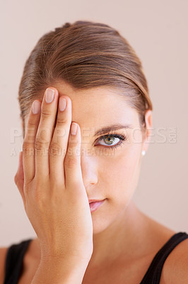 Buy stock photo Studio portrait of a young woman with one hand over one eye smiling at the camera
