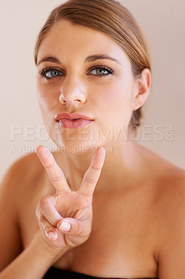 Buy stock photo Studio portrait of a young women giving the 'peace' sign to the camera