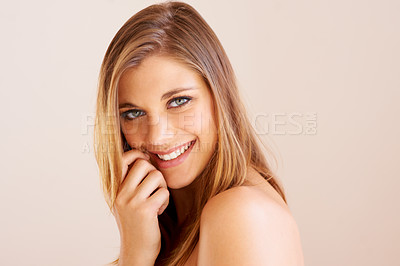 Buy stock photo Sideways portrait of an attractive young woman smiling at the camera