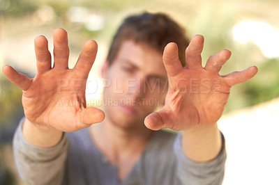Buy stock photo A handsome young man holding up his calloused hands