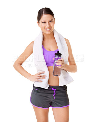Buy stock photo Studio shot of a sporty young woman with a towel draped over her shoulders and holding a water bottle isolated on white