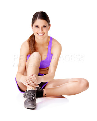 Buy stock photo Shot of a young women sitting on the floor and stretching her legs isolated on white