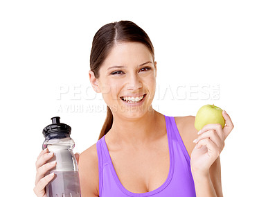 Buy stock photo Shot of a happy-looking young woman in gym clothing holding holding an apple and a water bottle isolated on white