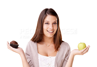 Buy stock photo Portrait of a beautiful young woman deciding between an apple and a muffin