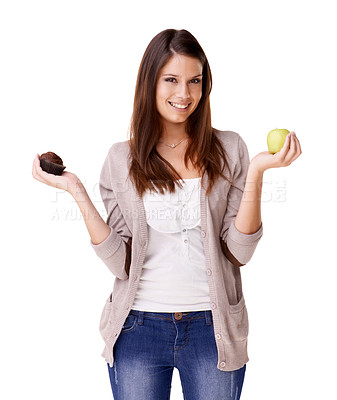 Buy stock photo Portrait of an attractive young woman deciding between an apple and a muffin