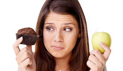 Buy stock photo A beautiful young woman deciding between an apple and a muffin