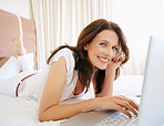 Portrait of a beautiful woman using laptop on bed