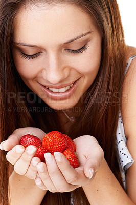 Buy stock photo An attractive young woman looking at the strawberries in her hands