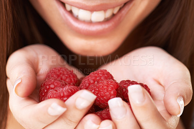Buy stock photo Cropped image of a happy young woman holding a bunch of raspberries