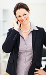 Happy woman speaking on cellphone at work