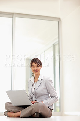 Buy stock photo Portrait of a cute happy business woman sitting on the floor , working on a laptop