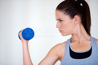 Buy stock photo Profile of an attractive young woman training with dumbbells and looking confident