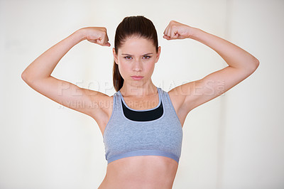 Buy stock photo Portrait of an attractive young woman pulling her biceps and looking confident