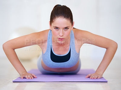Buy stock photo Portrait of a beautiful young woman doing push-ups in the gym