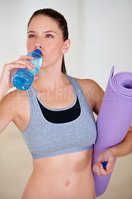 Buy stock photo An attractive young woman drinking a bottle of water